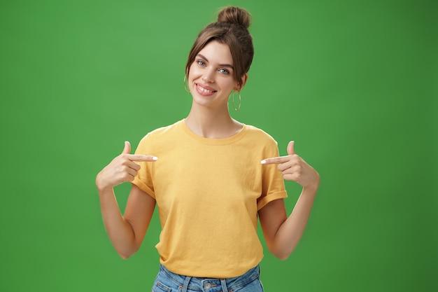 Kalm en beleefd vriendelijk ogende bekwame jonge vrouwelijke collega in geel t-shirt wijzend op zichzelf