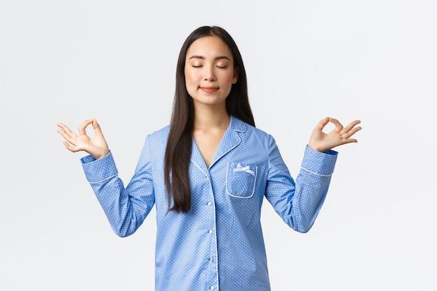 Kalm en gelukkig lachend aziatisch meisje in blauwe pyjama sluit de ogen, mediteert voor het slapengaan of in de ochtend, ziet er opgelucht en vredig uit, beoefent yoga-meditatie op een witte achtergrond.