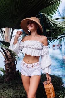 Kalm gelukkig stijlvolle mode meisje dragen witte gebreide korte broek en crop top met lange mouwen met picknick rieten mand handtas
