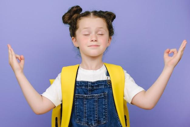 Kalm klein schoolmeisje dat mediteert met gesloten ogen, haar vingers in mudra-gebaar houdt, draagt gele rugzak, geïsoleerd over violette studioachtergrond. zen, mindfulness, balans en vrede concept