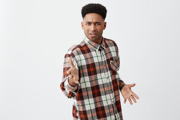 Kalm maar kerel. portret van verwarde jonge knappe zwarte man met zwarte huid en krullend haar in casual geruit overhemd, gebarend met handen, verward door zijn vriend die hem probeert te slaan.