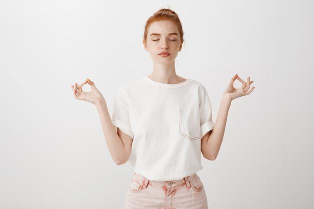 Kalm roodharig meisje dat geduldig blijft, ogen sluit en mediteert