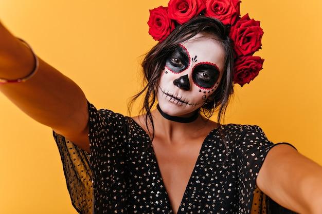 Kalm, slank meisje maakt selfie en pronkt met haar imago voor halloween. binnenportret van mooi model op oranje muur