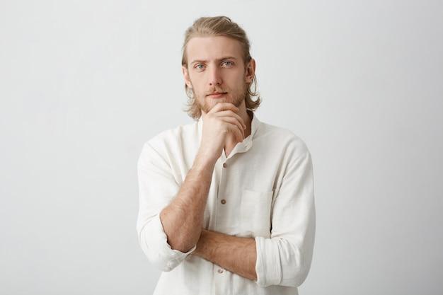 Kalm succesvolle europese bebaarde man met blond haar, hand op kin vasthouden