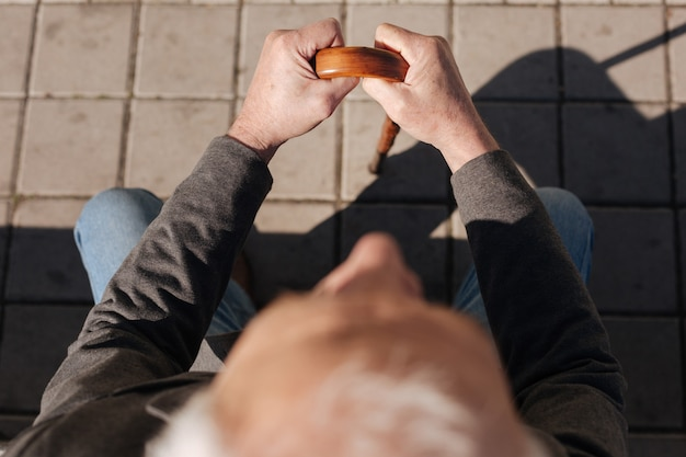 Kalm vermoeide opgeruimde man zittend op de bank rusten en koesteren in de zon