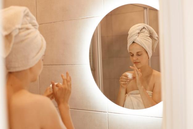 Kalme aantrekkelijke schattige vrouw die ochtendschoonheidsprocedures in de badkamer doet, voor de spiegel staat, crème in handen houdt, gewikkeld in een witte handdoek.