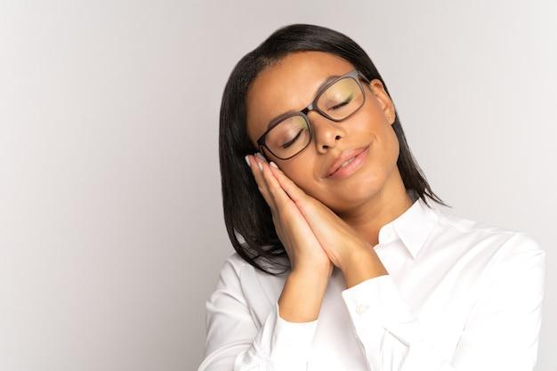 Kalme afro-amerikaanse zakenvrouw slaap liggend op gevouwen hand met gesloten ogen uitgeput moe op het werk
