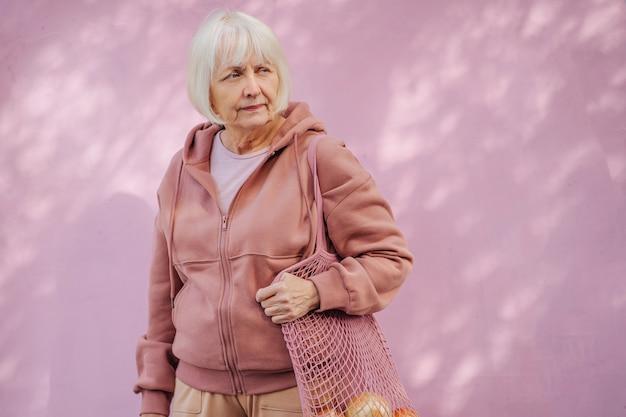 Kalme bejaarde vrouw in een gezellige hoodie met katoenen zak met kruidenierswinkel