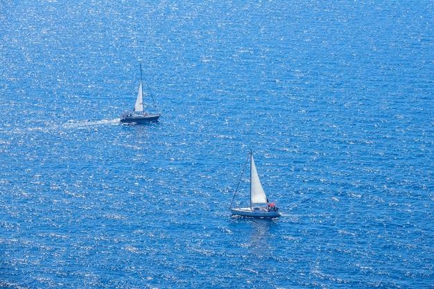 Kalme blauwe zee op een zonnige dag. twee zeiljachten met grootzeil vertrokken. luchtfoto