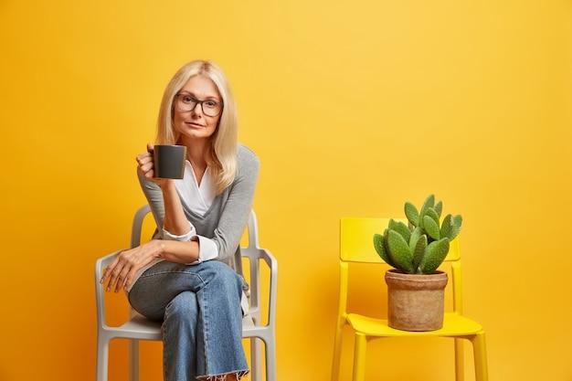 Kalme blonde vrouw zit op comfortabele stoel met drank kijkt zelfverzekerd en vormt in de buurt van ingemaakte cactus geniet van rustige sfeer. levensstijl concept