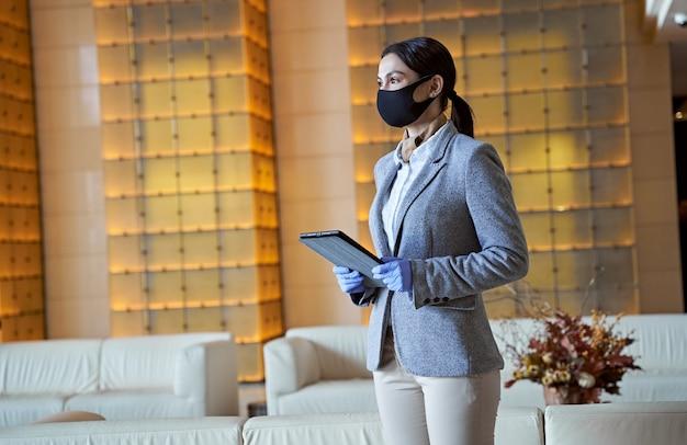Kalme dame in een pak die een tablet vasthoudt en wegkijkt. medisch masker en rubberen handschoenen volgens de veiligheidsmaatregelen