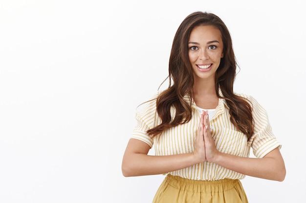 Kalme en ontspannen lachende aangename jonge vrouw met sproeten, donker kapsel, handpalmen tegen elkaar houden boven de borst, bidden of namaste gebaar, beleefd buigen als yoga-oefening uitvoeren, meditatie beëindigen
