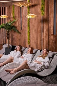 Kalme en ontspannen vrouwen die rusten na de spa in badjas
