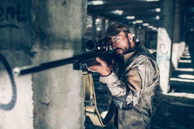 Kalme en stille volwassene kijkt door lens. hij neemt doel. guy staat naast kolom en wacht. jonge man zit in een grote hangar.