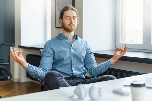 Kalme en vreedzame jonge zakenman met gesloten ogen die in bureau mediteren