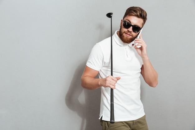 Kalme golfspeler die door de smartphone spreekt en club houdt