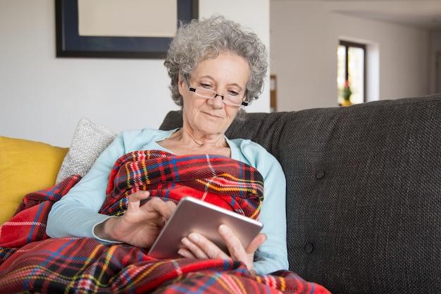 Kalme hogere vrouw die online boek met nieuwsgierigheid leest