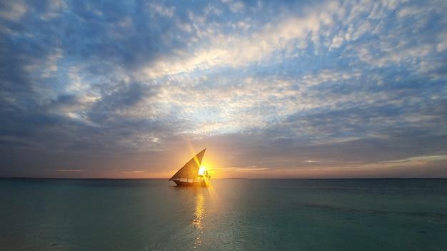 Kalme indische oceaan in de stralen van de ondergaande zon en de blauwe hemel met kleine wolken. een boot met een zeil gaat de oceaan op.