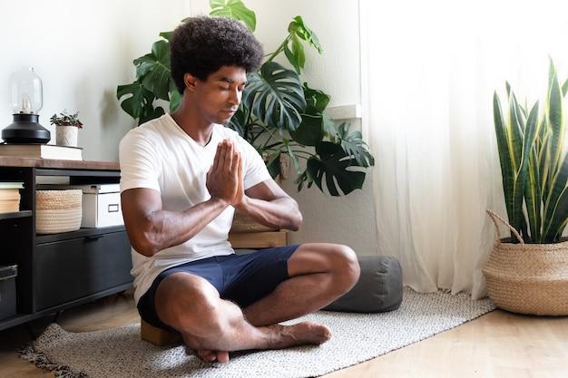 Kalme jonge afro-amerikaanse man die thuis mediteert met de handen in gebed kopieer de ruimte spiritualiteit