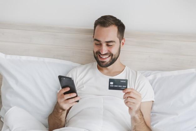 Kalme jonge bebaarde man liggend in bed met witte laken kussen deken in slaapkamer thuis