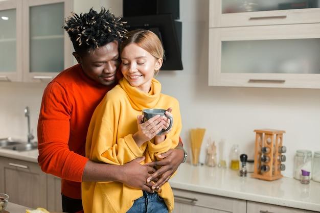 Kalme jonge dame die een kopje thee vasthoudt en glimlacht terwijl haar geliefde man achter haar rug staat en haar knuffelt