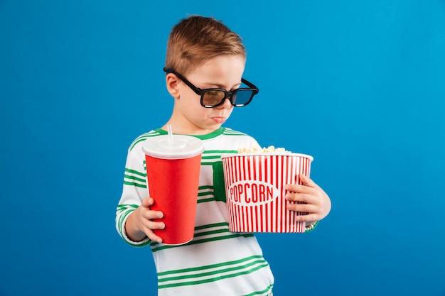 Kalme jonge jongen die in oogglazen de film voorbereidingen treft te bekijken