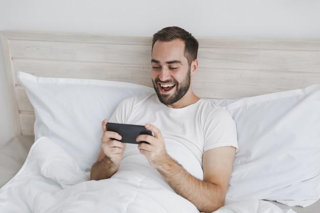 Kalme jonge knappe bebaarde man liggend in bed met witte laken kussen deken in slaapkamer thuis