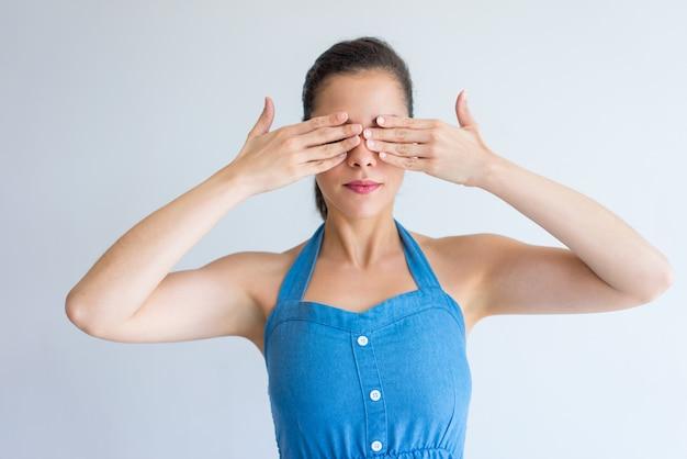 Kalme jonge vrouw in kleding die ogen behandelt met handen.