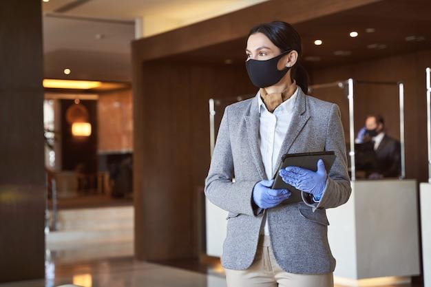 Kalme jonge vrouw met een moderne tablet in een hotellobby gekleed volgens de veiligheidsmaatregelen