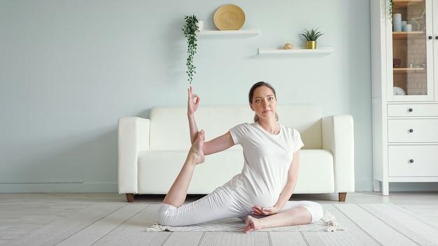 Kalme jonge, zwangere brunette vrouw doet ardha matsyendrasana die yoga-positie beoefent op de vloer in de buurt van de bank in een ruime kamer thuis