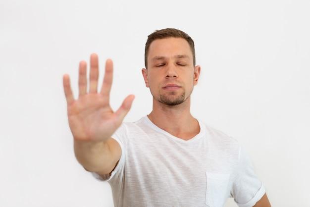Kalme knappe jonge man met gesloten ogen maken stop gebaar