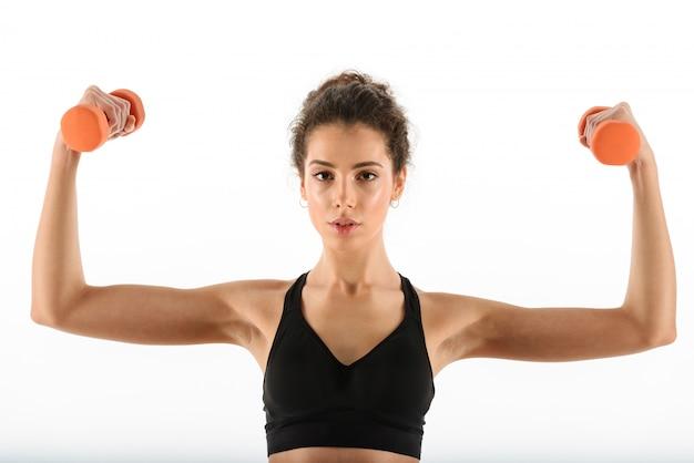 Kalme krullende donkerbruine geschiktheidsvrouw die oefening met domoren doen en haar bicepsen tonen