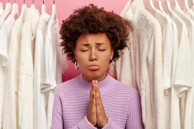 Kalme krullende vrouw houdt handpalmen tegen elkaar gedrukt, bidt voor welzijn, draagt gebreide trui, staat tussen witte kleren aan hangers, geïsoleerd op roze achtergrond.