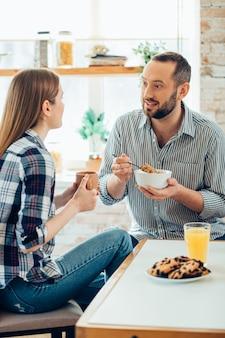 Kalme lachende man die met een lieve dame praat terwijl hij ontbijtgranen met haar eet