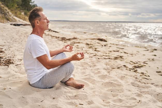 Kalme man zit in lotushouding terwijl hij oefent voor mindfulness aan de kust