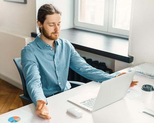 Kalme mannelijke kantoormedewerker die met gesloten ogen mediteert op het werk