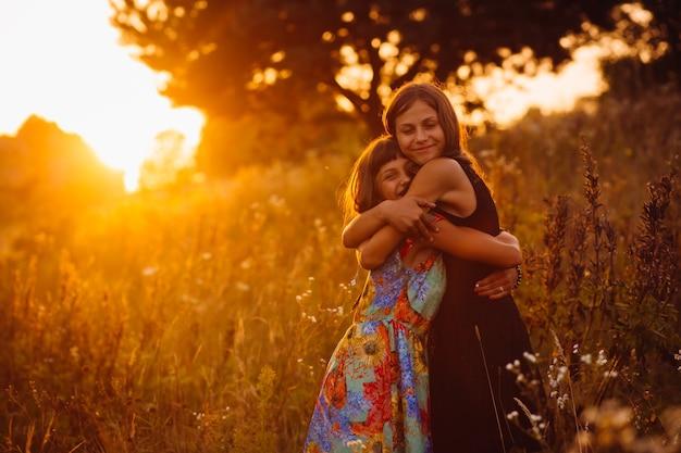 Kalme meisjes staan op het veld van de avond
