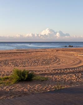 Kalme ochtend op leeg strand met een autoband wordt afgedrukt op zand, met zee en wolken op de achtergrond
