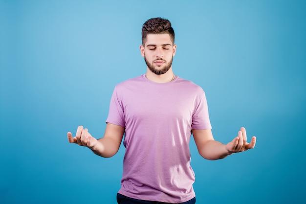 Kalme ontspannen jonge mens die om gebaar mediteren tonen geïsoleerd op blauw