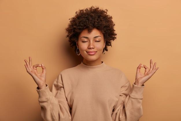 Kalme opgeluchte donkere vrouw haalt diep adem, houdt de handen zijwaarts in zen gessture, bereikt nirvana en beoefent yoga, staat met gesloten ogen, staat stressvrij tegen bruine muur