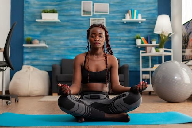 Kalme rustige zwarte vrouw die ogen gesloten houdt zittend op yogamat tijd doorbrengend op spiritualiteit genees...
