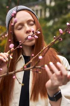 Kalme sensuele roodharige vrouw inhaleert de geur van bloeiende magnoliaboom en raakt boomtakken aan die staan...