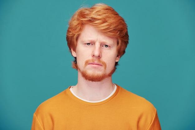 Kalme spirituele jonge roodharige man met baard die namaste-gebaar maakt terwijl hij mediteert met gesloten ogen tegen blauwe muur