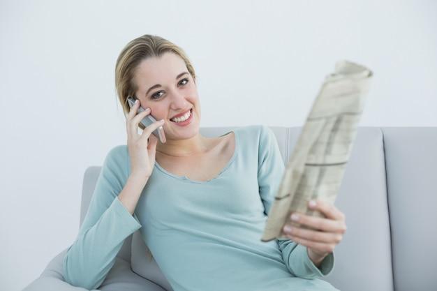 Kalme vrouw die terwijl holdingskrant telefoneert en op laag zit
