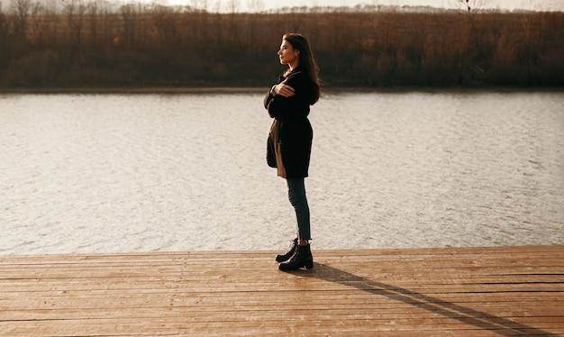 Kalme vrouw stond op pier in de buurt van meer bij zonsondergang