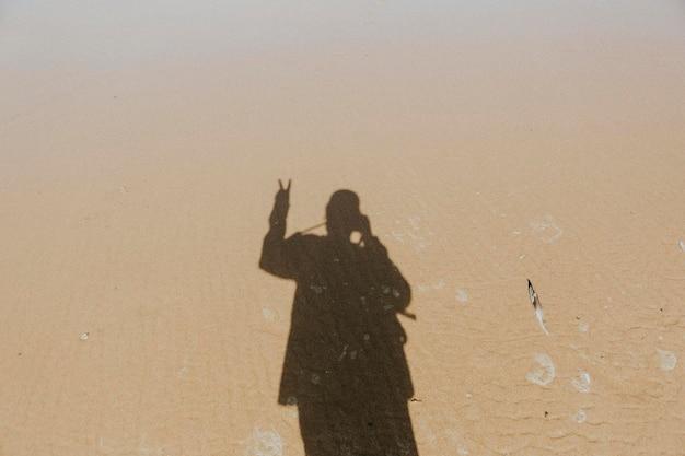 Kalme wateren over het zand met een schaduw van een man