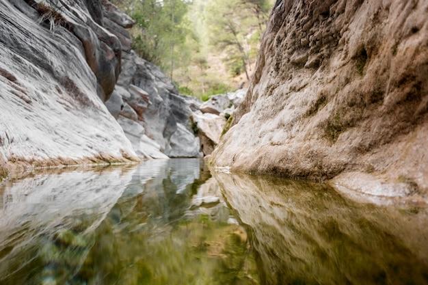 Kalme waterloop die in de rotsachtige bodem stroomt en het bos in zijn wateren weerspiegelt