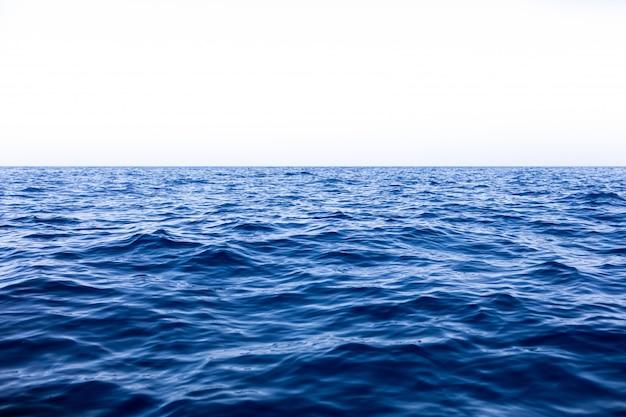 Kalme zee oceaan en blauwe hemelachtergrond