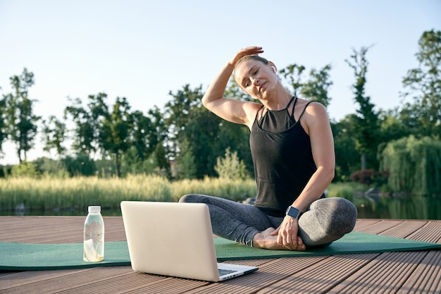 Kalmeer je geest, atletische mooie vrouw van middelbare leeftijd die instructievideo's bekijkt op een laptop terwijl