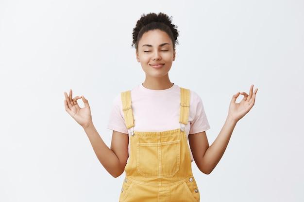 Kalmeren en stress van binnen wegnemen. rustige en schattige knappe vrouw met donkere huid in gele trendy overall, hand in hand aan beide kanten met zen-gebaar, mediteren of yoga doen